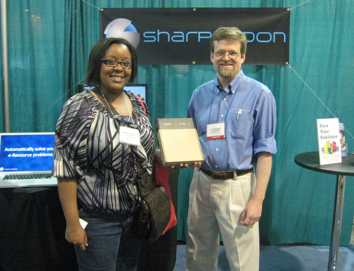 Kimberly Taylor receiving Amazon Kindle prize from John Weible, President of Sharp Moon Inc.